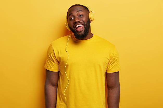 Откровенный снимок счастливого афроамериканца, который слушает подкаст с песнями и носит современные стереонаушники.