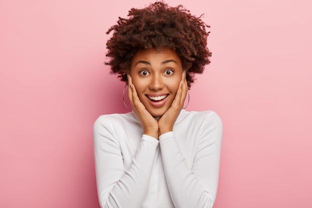 Откровенный снимок счастливой темнокожей девушки с довольным выражением лица, позитивной улыбкой, касанием щек, повседневным свитером с высоким воротником, моделями в помещении, рада получить потрясающее предложение или предложение