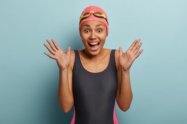 과잉 감정적 인 아프리카 계 미국인 여성의 솔직한 샷은 손바닥을 들고 행복한 반응을 보이고 검은 수영복을 입습니다.