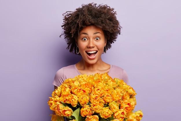 과감한 아름답고 어두운 피부를 가진 여성의 솔직한 샷은받은 튤립에서 긍정적으로 반응합니다.