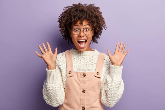 アフロの髪の、感情に訴えるうれしそうな暗い肌の若い女性の率直なショットは、2つの手のひらを上げます