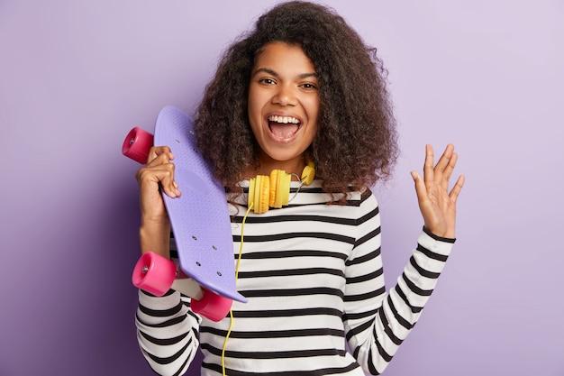 巻き毛の髪型、手のひらで波、スケートボードを運ぶポジティブな暗い肌の女性モデルの率直なショット