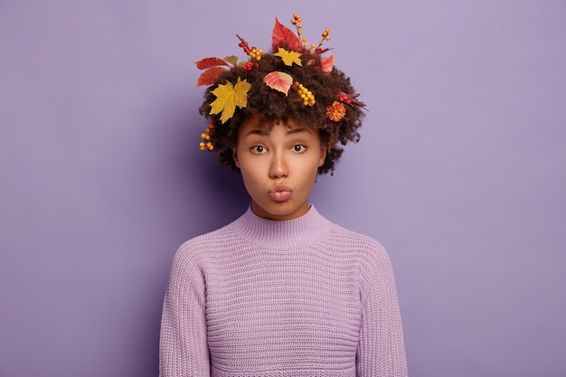 슬픈 곱슬 머리 여자의 솔직한 샷은 공격적인 얼굴을 찡 그리기, 입술을 둥글게 유지, 가을 산책, 비오는 날씨를 좋아하지 않으며 캐주얼 니트 스웨터를 입고 실내에 서 있습니다.