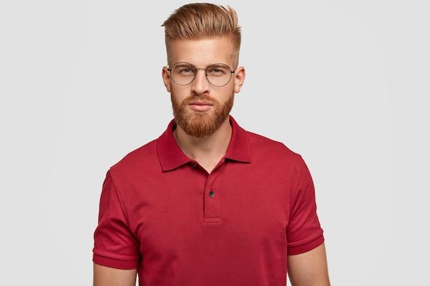 セクシーな髪とあごひげを生やした、自信に満ちた真面目な白人男性の率直なショットは、カジュアルな服装で、神秘的な表情で直接見え、眼鏡をかけ、白い壁に隔離されています