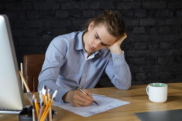 Откровенный снимок стильного молодого европейского архитектора, работающего в офисе, проверяющего чертежи ручкой, с грустным серьезным взглядом, усталого и сонного, стационарных предметов, кружки и компьютера на деревянном столе