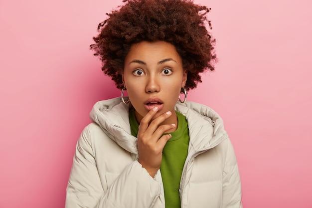 겨울 옷을 입은 놀란 여자의 솔직한 샷은 떨어 뜨린 턱에 손을 대고 놀랍게 쳐다보고 분홍색 배경 위에 격리합니다.