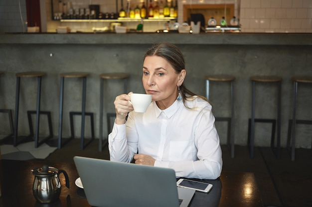 Откровенный снимок вдумчивой зрелой бизнес-леди в формальной рубашке, наслаждающейся кофе во время обеда, сидящей в кафе с универсальным ноутбуком и сотовым телефоном с пустым экраном на столе. бизнес, возраст и технологии