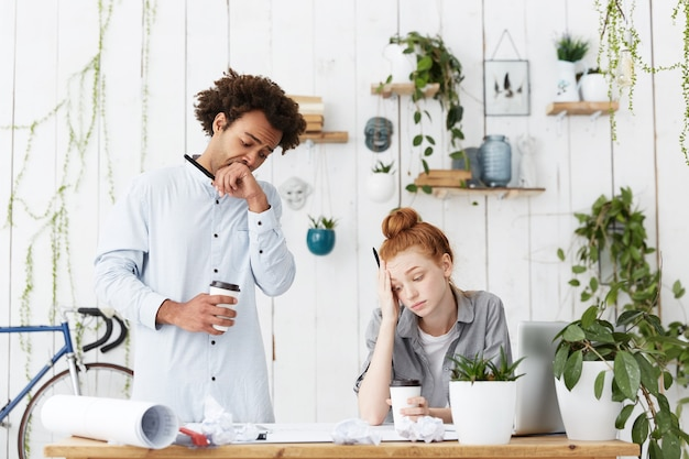 Откровенный снимок двух усталых и сонных молодых мужчин и женщин-архитекторов, ожидающих крайнего срока