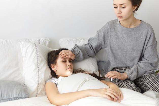 Откровенный снимок взволнованной расстроенной молодой женщины, сидящей в спальне, держащей руку на лбу своей больной дочери.