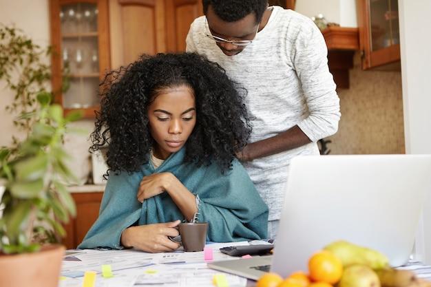一緒に財政を通じて働く若いアフリカ系アメリカ人カップルの率直なショット