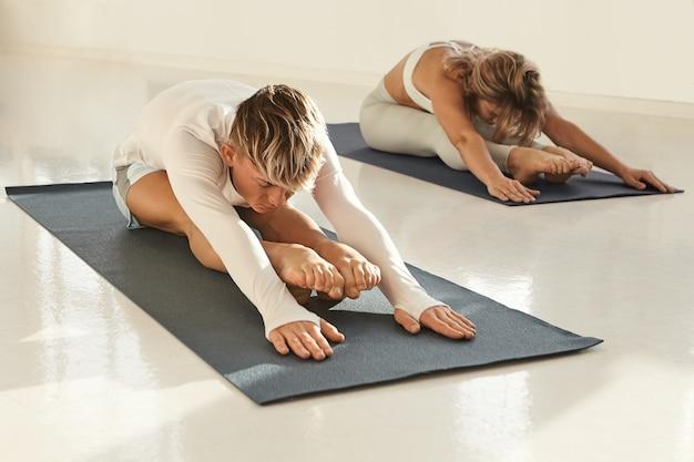 젊은 유럽 남성과 여성의 실내 요가 연습, 스트레칭, 매트에 앉아 바닥에 손 놓기의 솔직한 샷. 스포츠 클럽에서 운동하는 두 명의 건강한 활동적인 요가, 앞으로 구부리기