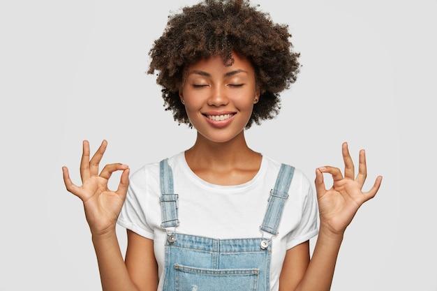 Il colpo schietto di una bella donna di colore mostra il gesto giusto o zen