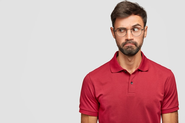 Candid shot of puzzled caucasian male with dark stubble looks suspiciously aside, raises eyebrows, wears red t-shirt, notices something on blank space. people and facial expressions concept.