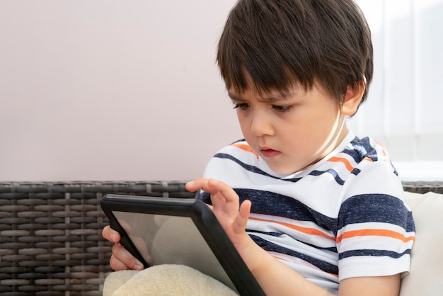 Candid shot of school kid playing game on tablet with serious face, cropped shot child boy concentrated watching cartoon on touch pad, child relaxing at home on weekend.