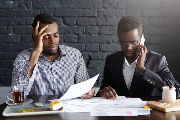 Candid shot of serious afro-american colleagues in formal wear working together in office: man in shirt looking through papers while male wearing glasses having phone conversation, looking worried