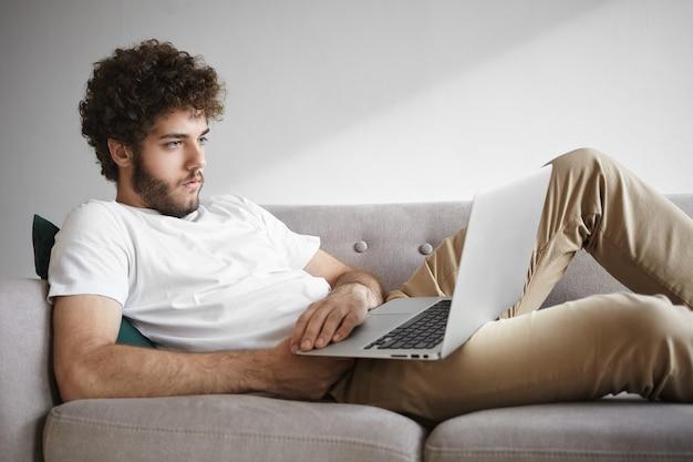 Colpo schietto di giovane maschio con la barba lunga concentrato serio in maglietta bianca che naviga in internet su un laptop generico, guarda film o legge articoli online, usando il wifi gratuito, seduto sul divano a casa