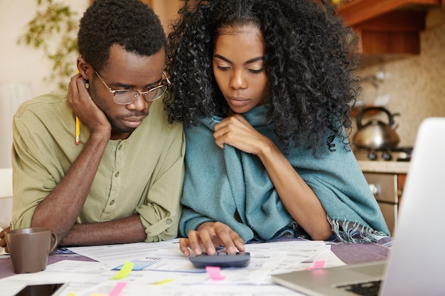 Candid shot of stressed african couple reviewing their finances at home