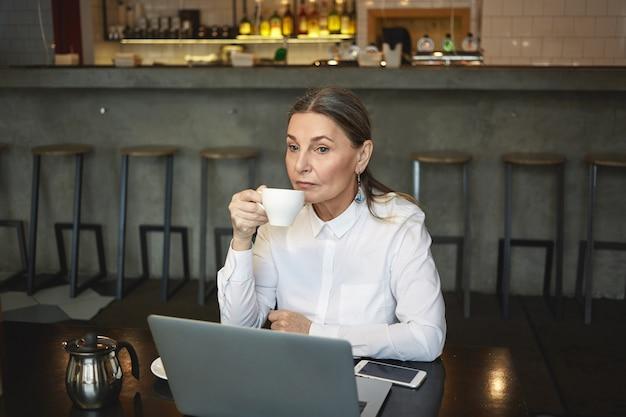 Candid colpo di premurosa imprenditrice matura in camicia formale gustando un caffè durante il pranzo, seduto al bar con laptop generico e telefono cellulare con schermo vuoto sul tavolo. affari, età e tecnologia