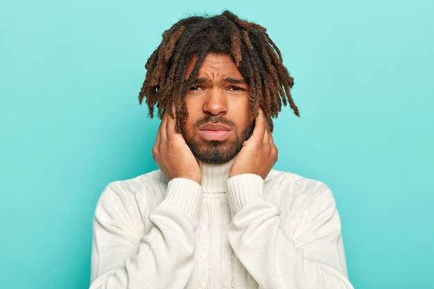 Candid shot of unhappy dark skinned man smirks face, touches face and looks unpleasantly at camera, dressed in casual white sweater, suffers from painful feelings, isolated over blue background.