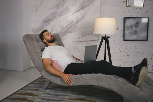 Candid shot of unshaven young male in shoes lying comfortably on gray couch with portable computer on his lap, having nap or meditating, keeping his eyes closed, listening to relaxing music