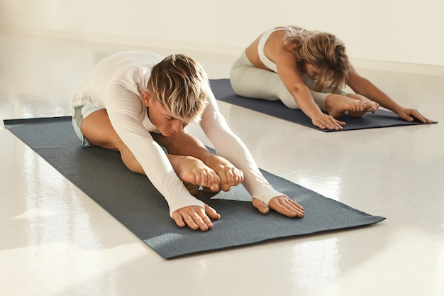 Candid shot of young european male and female practicing yoga indoors, stretching, sitting on mats and placing hands on floor. two healthy active yogis exercising in sport club, doing forward bend