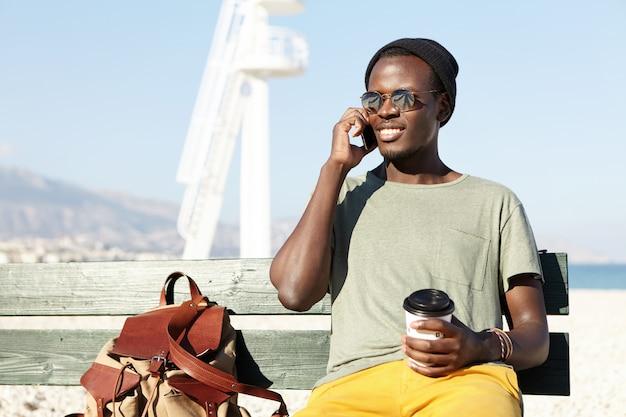 陽気な浅黒い肌の学生が屋外でバックパック付きの木製ベンチに座って、携帯で友達と素敵な電話で話し、幸せそうに笑って、テイクアウトのコーヒーを楽しんでいる様子の率直なアーバンショット