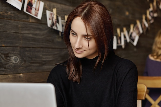 Candid view of attractive brunette female translator in black dress using wifi at cafe