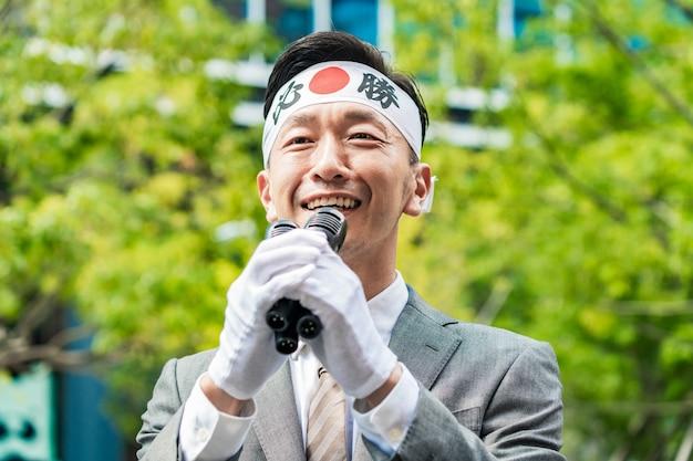 街頭演説を行う選挙の候補者。ヘッドバンドに書かれている文字は日本語で、意味は「必ず勝つ」です。