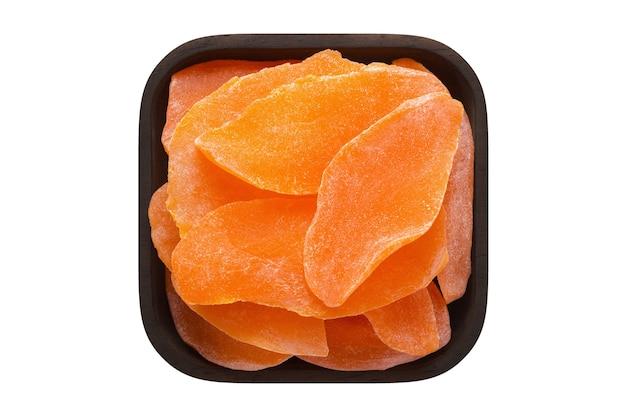 砂糖漬けの果物、白い壁に隔離された正方形のボウルに砂糖と乾燥マンゴー。有機食品、上面図。
