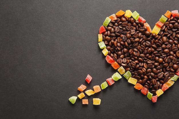 矢印の付いたハートの形の砂糖漬けの果物、デザインのために黒い背景に分離された茶色のコーヒー豆。休日のコンセプトである2月14日の聖バレンタインデーカード。広告用のスペースをコピーします。