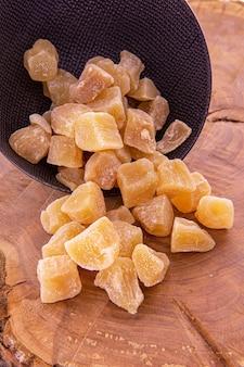 Засахаренный имбирь, нарезанный кубиками, высыпанный из темной чашки на деревянную