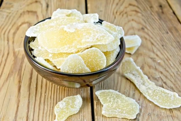 나무 판 배경에 그릇에 설탕에 절인 생강