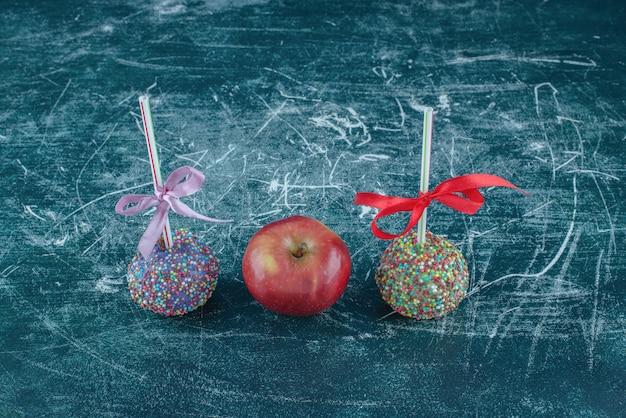 Lecca lecca canditi e una mela su sfondo blu. foto di alta qualità