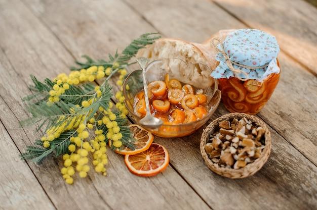 Цукаты из апельсиновой спиральной цедры с сахарным сиропом в стеклянной банке и тарелка возле блюдца с грецкими орехами, мимозой и хлебом на деревянном столе