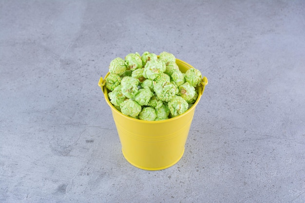 Candied popcorn heaped into a yellow bucket on marble surface