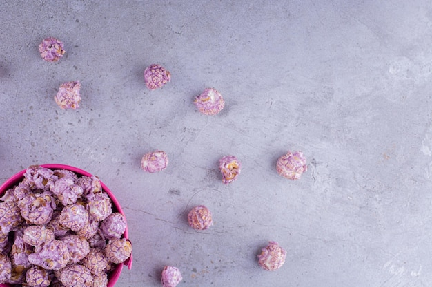 Candied popcron inside and scattered around a small bucket on marble background. high quality photo