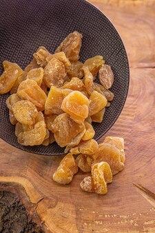 Цукаты из имбиря в сахаре вылили из темной чашки на деревянный стол