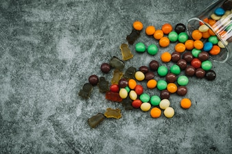 Candies and marmalade scattered on table