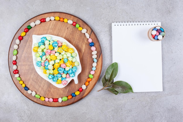Candies in and around an ornate platter on a wooden tray next to a notepad adorned with leaves on marble background. high quality photo