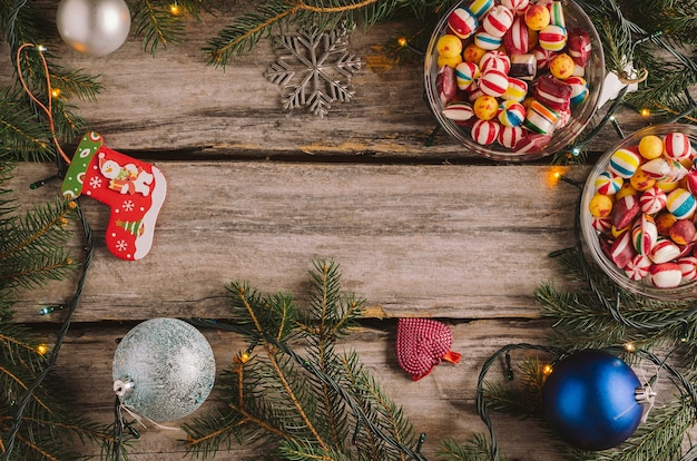 Candies, christmas baubles and spruce tree branches on a wooden surface