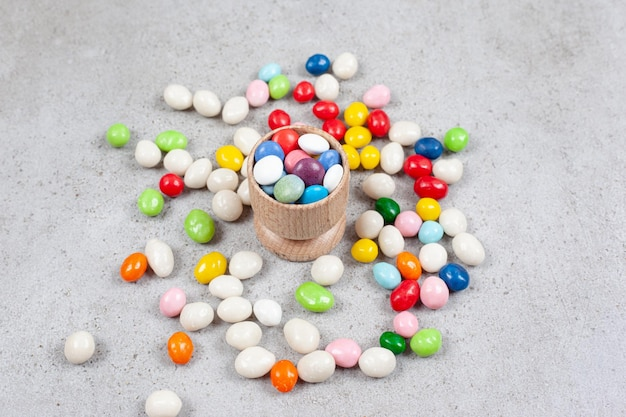 Candies filled into a tiny bowl and scattered around on marble surface