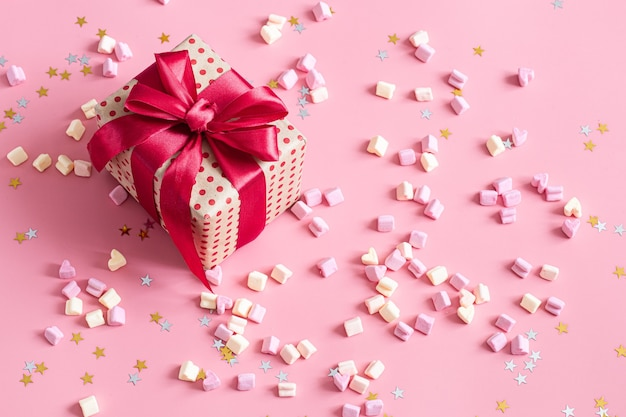 Candies and gift box with red bow on pink surface.