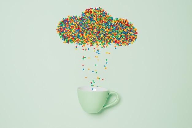 緑の背景に雨雲の形をしたキャンディー。天気の概念。