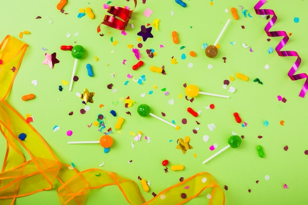 Candies and lollipops with confetti and curled streamer on green background