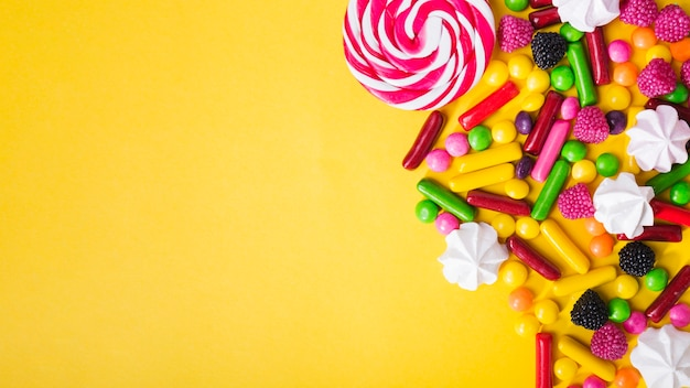 Candies and marshmallows on yellow background