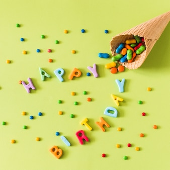 Candies spilling from waffle ice cream cone on happy birthday over green surface