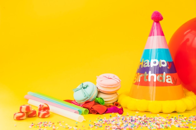 Candies; straw; deflated balloon; macarons and paper hat on yellow background