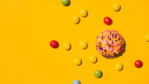 Candies with sprinkle donut on yellow background
