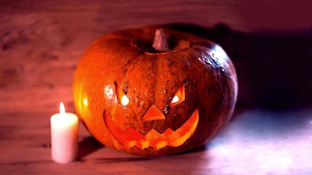 木製のテーブルの上のキャンドルと不気味な笑顔のハロウィーンのカボチャ