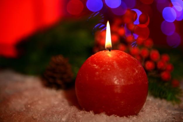 明るい背景の背景に木製のテーブルの上のキャンドルとクリスマスツリーのつぼみ
